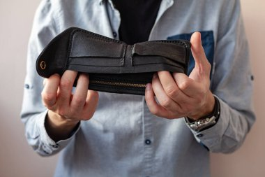 men's hands hold an empty purse. A wallet with little money in it. The concept of poverty and bankruptcy