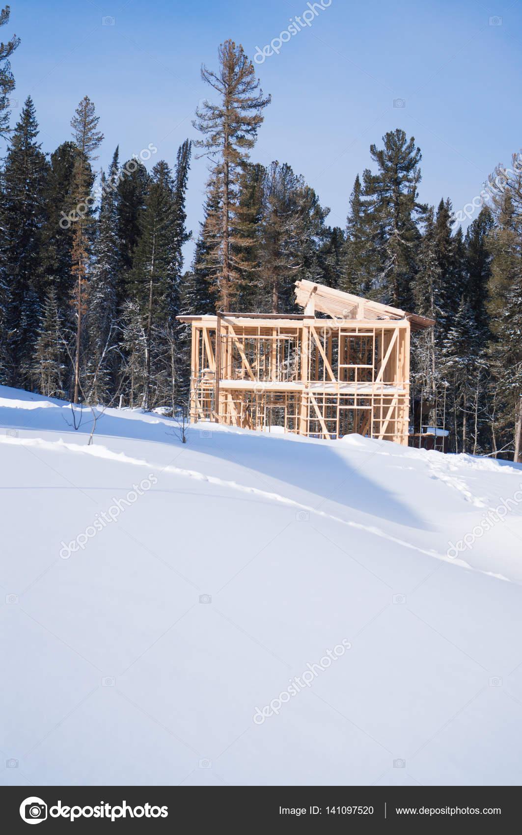 En la una pendiente de nieve es una casa de marco de madera sobre un ...