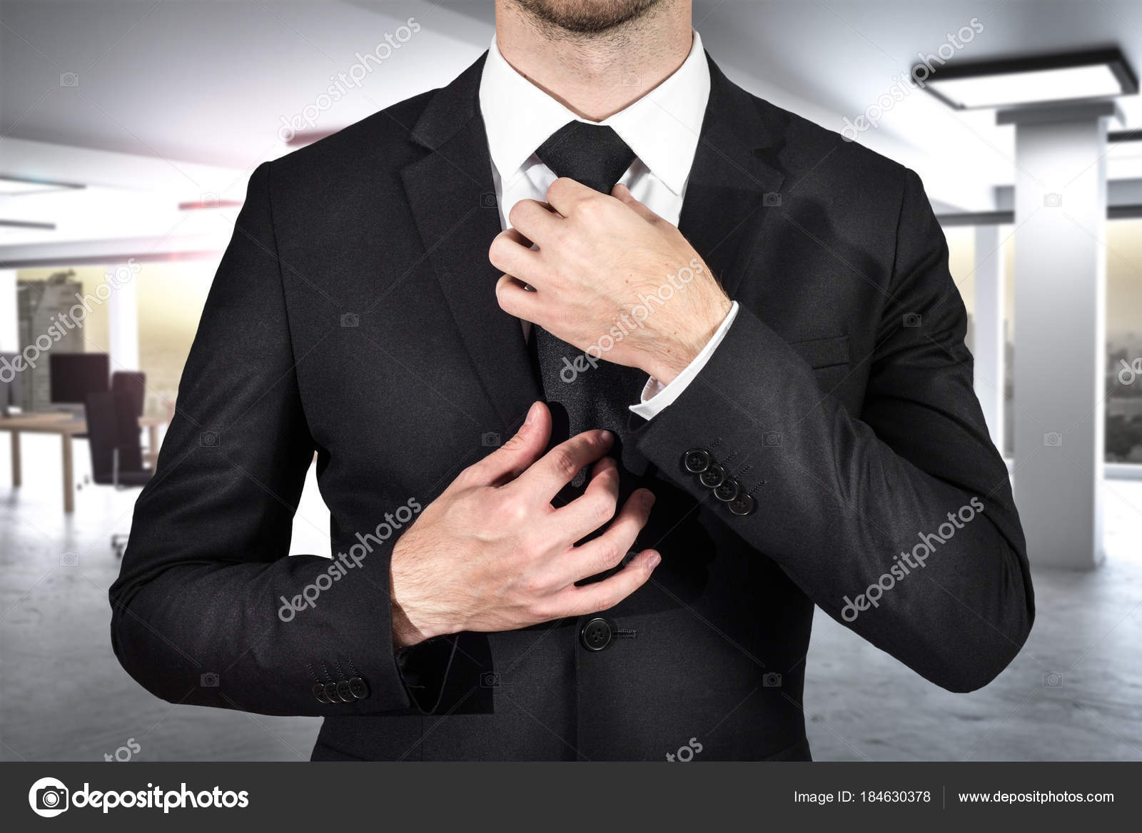 businessman in black suit ties his black tie in modern office photo by imilian