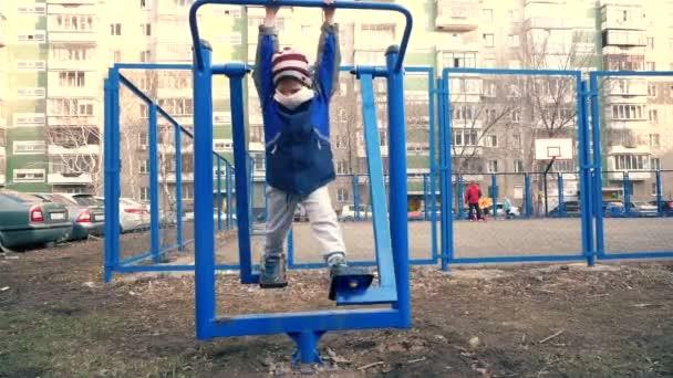 Sport treiben in Quarantäne. Ein Junge in medizinischem Verband treibt auf einem Simulator im Hof Sport. Pandemie-Sport