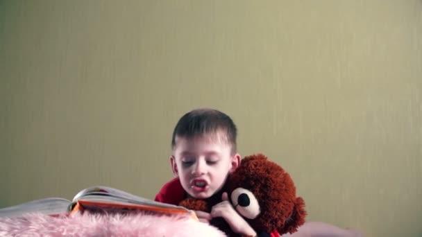 Das Kind liegt zu Hause und umarmt ein Bärenspielzeug und liest ein Kinderbuch.