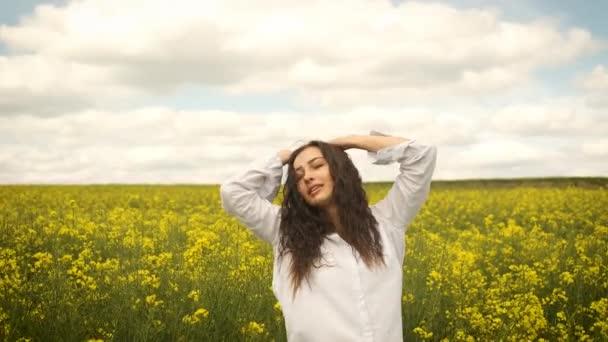 Fröhliches Mädchen im frühlingsgelben Raps läuft vor die Kamera und lächelt herzlich. Gelbe Blumen in der schönen Natur
