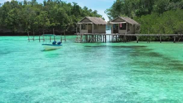 krásná modrá laguna s některými bambusové chýše kordiris homestay palmy v přední straně gam ostrov západ papuan raja ampat indonésie