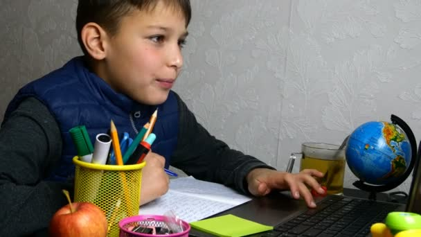 Távolságtanulás, e-tanulás. Az iskolás fiú online tanul, és iskolai leckét ír a jegyzetfüzetével karantén alatt. Asztalon ülök az iskolai felszereléssel. Közelkép portré.