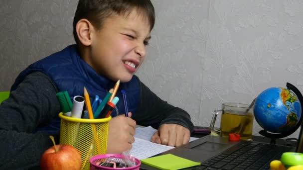 Távolságtanulás. Vicces iskolás fiú online tanul, és iskolai házi feladatot csinál a jegyzetfüzetével karantén alatt. Grimaszol és bolondozik. Közelkép portré.