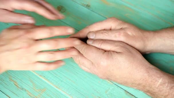 Die Hand der Frau hält den Mann und streichelt ihn. Konzept der Einheit der Familie. Nahaufnahme.