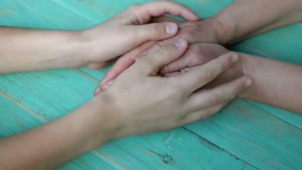 A gyerekek fogják egymás kezét és simogatják a nőket. Családi egységkoncepció. Közelkép.