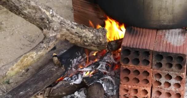 Detailní kuchyňský oheň s dřevěným ohněm. Měsíční Nový rok. Rýžový koláč. Kamna na uhlí. Vařte ručně. Původní oheň. Video 4K