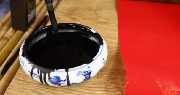 psaní kaligrafie na červeném papíru v Novém roce. Namočte hladinu vody štětcem a inkoustem. Nástroje na psaní Asiatů. Starověké asijské písmo. Asijský styl psaní. Červený papír. Video 4K