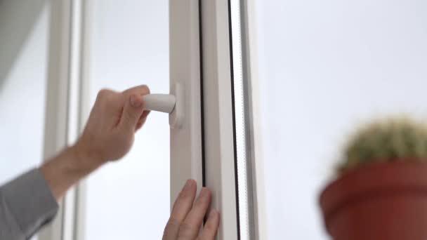 Muž otevře a zavře bílé plastové okno za klikou.