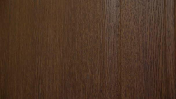 4K. Pohled z boku, žena klepe pěstí na hnědé dřevěné dveře. Zavřít - nahoru z ruky .