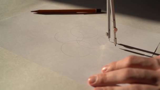 4K. Workplace designer. The hand of a teenager draws on a Sunny day on a white sheet of paper Circinus / compass .