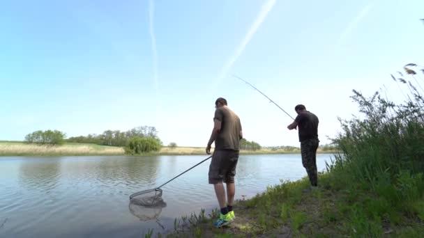 4K. Két halász a parton két fonórúddal horgászik, és örülnek, hogy harapnak. Ez a berendezés alkalmas olyan halak, mint: ponty, fehér Ámor, keszeg.