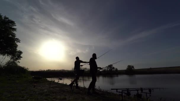 4K. Dva rybáři na břehu rybaří dvěma točícími se pruty a jsou rádi, že koušou. Toto zařízení je vhodné pro takové ryby, jako jsou: kapři, bílí Amor, cejn.