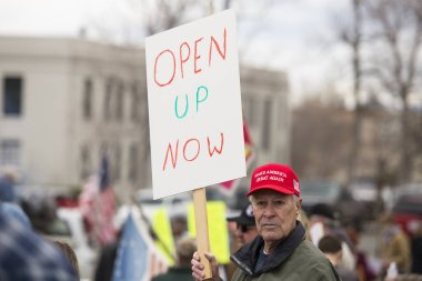 Helena, Montana - April 19, 2020: Protestor holding sign at a protest rally over the shutdown and stay at home orders due to fear about Coronavirus. Old man wearing Make America Great Again hat.