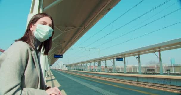 Egy maszkos nő vár a vasútállomáson.