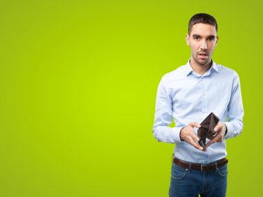 Shocked businessman without money on green background