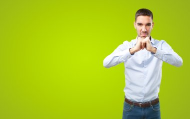 Businessman with a gesture of strength on green background