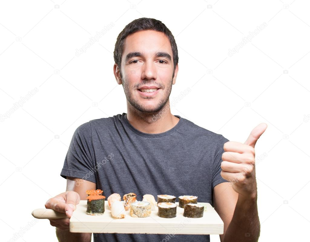 young man eating sushi with a gesture of approval ストック写真