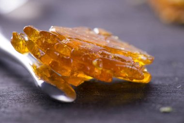 Piece of cannabis oil concentrate aka shatter with dabbing tool
