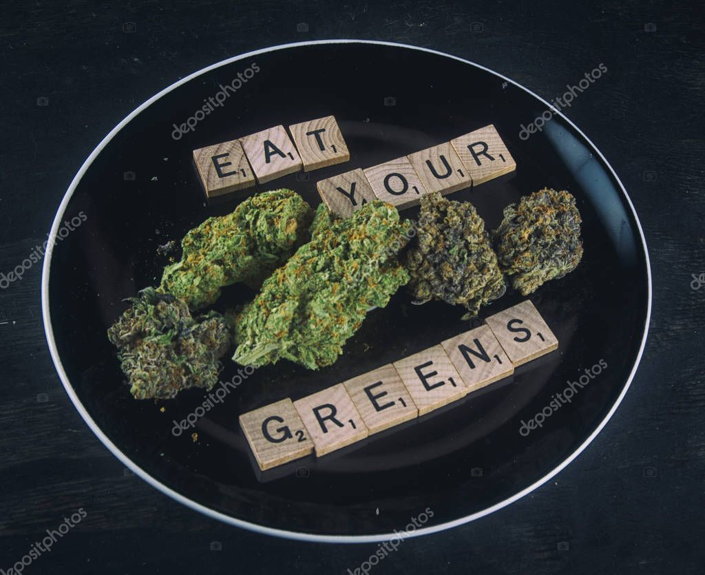Plate with cannabis buds on black - infused medical marijuana co