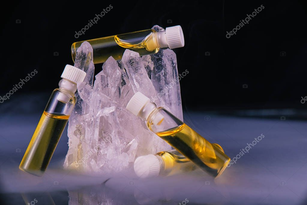 Detail of cannabis oil containers and quartz crystal isolated on