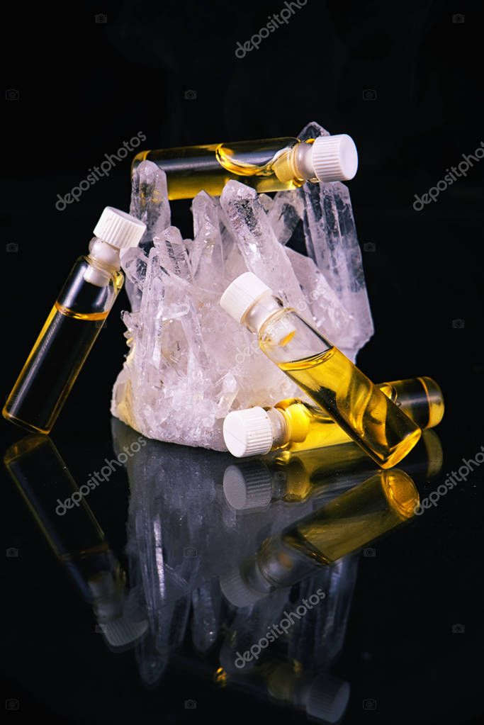 Cannabis oil container and quartz crystal isolated on black