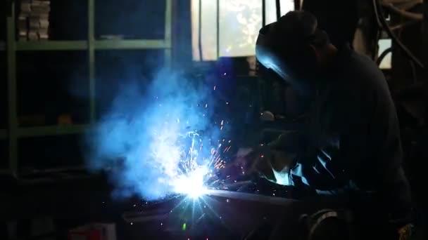 Muž svářečka nosit maskované pracovní oděvy v továrně pracuje svařováním.