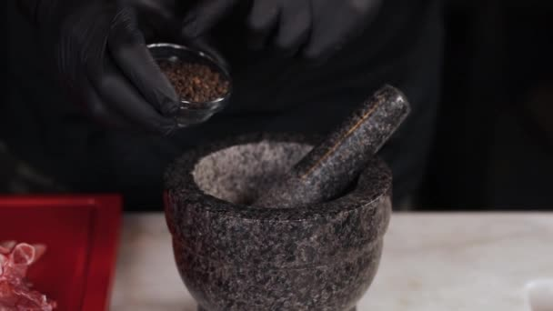 the cook prepares spices in a stone mortar