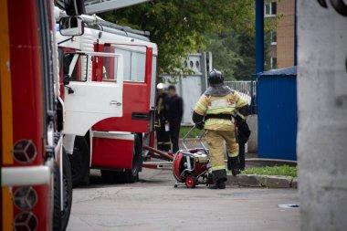 İtfaiyeci, yangından sonra sırtını itfaiye arabasının yanına dayayıp dinleniyor. arkaplan bulanık