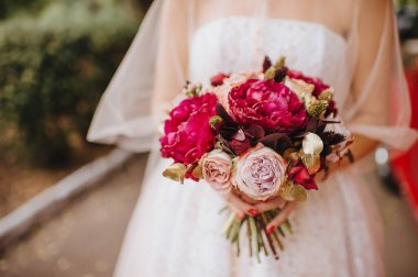 Bride's bouquet close-up, the bouquet consists of red peonies rose. The bride holds the bouquet