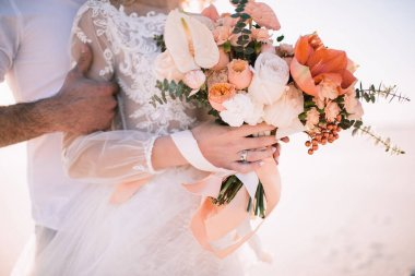 Close-up of a brides bouquet of amaryllis, anthurium, roses, carnations, eucalyptus in white-peach shades. The bride in a lace white dress holds a bouquet in her hands, the groom hugs her.