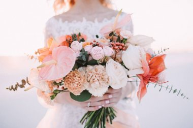 Close-up of a brides bouquet of amaryllis, anthurium, roses, carnations, eucalyptus in white-peach shades. The bride in a lace white dress holds a bouquet in her hands.  White sand