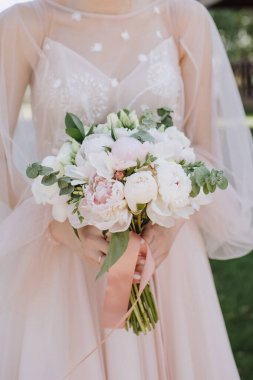 Bride's bouquet close-up, the bouquet consists of white and pink peonies, eucalyptus. The bride dressed in pink wedding dress holds the bouquet