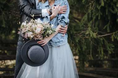 The bride in a denim jacket holds a hat and a bouquet in white and purple shades. Groom hugs her from behind