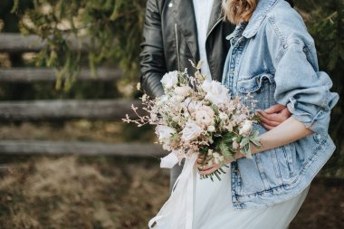 The bride in a denim jacket and hat holds a bouquet in white and purple shades. Groom hugs her from behind