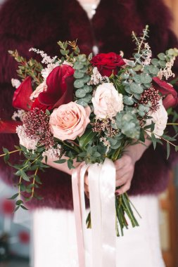 Bride's bouquet close-up, the bouquet consists of red and white roses and eucalyptus. The bride holds the bouquet