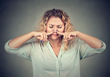 woman pinches nose with fingers looks with disgust something stinks