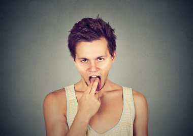 disgusted man with finger in mouth displeased ready to throw up