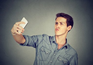 funny looking man taking pictures of himself with smartphone