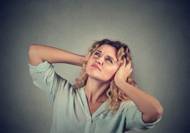 annoyed, unhappy, stressed woman covering her ears, looking up