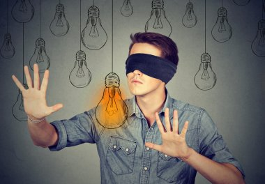 Blindfolded man walking through light bulbs searching for idea