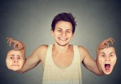 Photo Smiling man holding two different emotion masks