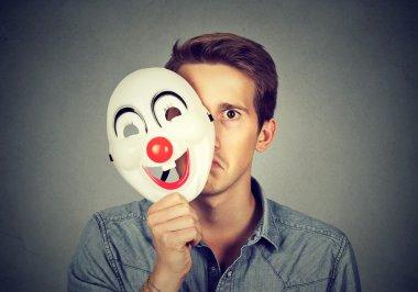 Young sad man hiding behind happy clown mask