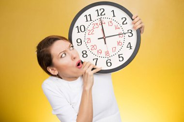 Stressed woman holding clock looking anxiously running out of time