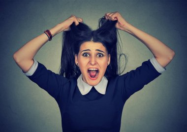 Stress. Woman stressed is going crazy pulling her hair in frustration