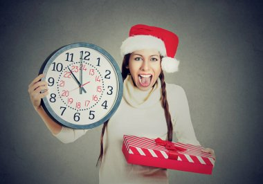 happy woman wearing red santa claus hat holding clock gift box