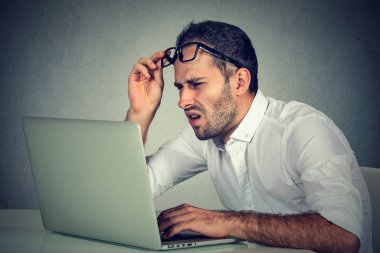 man with glasses having eyesight problems confused with laptop software