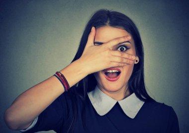 Surprised woman looking between fingers
