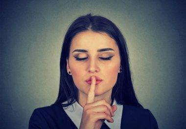 secretive woman placing finger on lips shh quiet